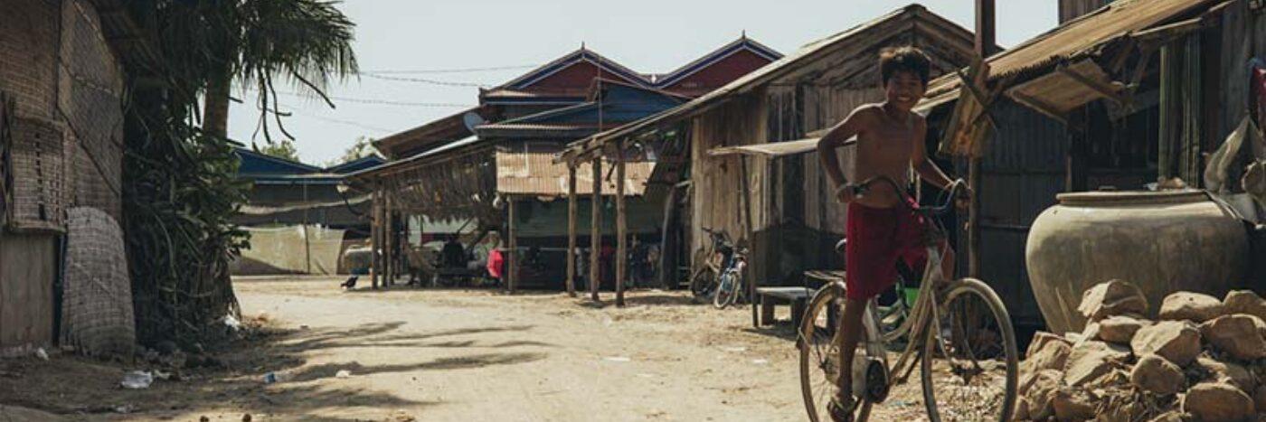Cycling through a rural village in Cambodia